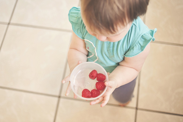 baby holding raspberries